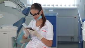 Ο θηλυκός οδοντίατρος χρησιμοποιεί το κινητό τηλέφωνο στην οδοντική κλινική φιλμ μικρού μήκους