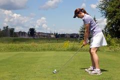 Ο θηλυκός παίκτης γκολφ προετοιμάζεται να τοποθετήσει στο σημείο αφετηρίας μακριά Στοκ φωτογραφίες με δικαίωμα ελεύθερης χρήσης