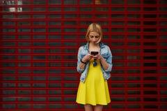 Ο θηλυκός σπουδαστής hipster στο φόρεμα που χρησιμοποιεί το κινητό τηλέφωνο για συνδέει με το ραδιόφωνο στοκ εικόνες