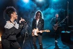 Ο θηλυκός τραγουδιστής με το μικρόφωνο και ο βράχος - και - κυλούν τη ζώνη εκτελώντας τη μουσική σκληρής ροκ Στοκ Φωτογραφίες