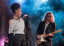 Ο θηλυκός τραγουδιστής με το μικρόφωνο και ο βράχος - και - κυλούν τη ζώνη εκτελώντας τη μουσική σκληρής ροκ Στοκ Εικόνες