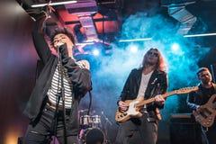 Ο θηλυκός τραγουδιστής με το μικρόφωνο και ο βράχος - και - κυλούν τη ζώνη εκτελώντας τη μουσική σκληρής ροκ Στοκ φωτογραφίες με δικαίωμα ελεύθερης χρήσης