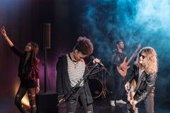 Ο θηλυκός τραγουδιστής με το μικρόφωνο και ο βράχος - και - κυλούν τη ζώνη εκτελώντας τη μουσική σκληρής ροκ Στοκ εικόνα με δικαίωμα ελεύθερης χρήσης