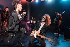 Ο θηλυκός τραγουδιστής με το μικρόφωνο και ο βράχος - και - κυλούν τη ζώνη εκτελώντας τη μουσική σκληρής ροκ Στοκ φωτογραφία με δικαίωμα ελεύθερης χρήσης