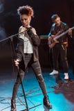 Ο θηλυκός τραγουδιστής με το μικρόφωνο και ο βράχος - και - κυλούν τη ζώνη εκτελώντας τη μουσική σκληρής ροκ Στοκ Εικόνα