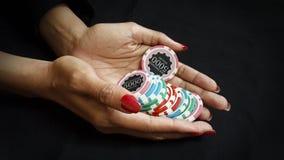 Ο θηλυκός φορέας πόκερ κρατά τα τσιπ πόκερ της για να κάνει ένα στοίχημα στοκ εικόνες