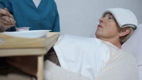 Ο ιατρικός εργαζόμενος που βοηθά την αδύνατη γυναίκα για να φάει, φροντίζει κατάλληλα για τον ασθενή στο νοσοκομείο απόθεμα βίντεο