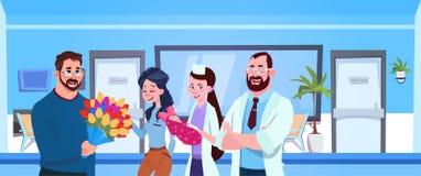Ο ιατρός και η νοσοκόμα δίνουν νεογέννητο στους ευτυχείς γονείς στο νοσοκομείο ελεύθερη απεικόνιση δικαιώματος