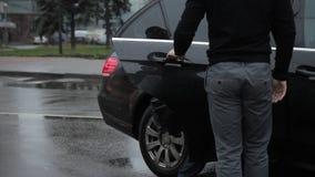 Ο ιδιωτικός οδηγός ανοίγει την πόρτα του ακριβού αυτοκινήτου πολυτέλειας για το VIP αρσενικό πελάτη του απόθεμα βίντεο