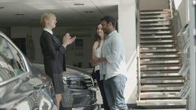 Ο διευθυντής δίνει τα κλειδιά αυτοκινήτων ` s στο ευτυχές ζεύγος στην αίθουσα εκθέσεως αυτοκινήτων απόθεμα βίντεο