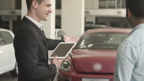 Ο διευθυντής με την ταμπλέτα παρουσιάζει τα αυτοκίνητα στον πελάτη στην αίθουσα εκθέσεως αυτοκινήτων απόθεμα βίντεο