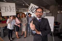 Ο διευθυντής που παρουσιάζει μακρύ δάχτυλο, υπάλληλοι που κρατά τις αφίσες με τις λέξεις χτυπά και αριθ. Στοκ Εικόνες