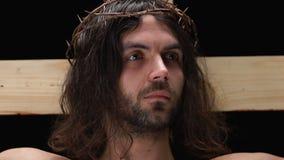 Ο Ιησούς Χριστός στην κορώνα των αγκαθιών στο σταυρό που υποφέρει για τις αμαρτίες λαών απόθεμα βίντεο