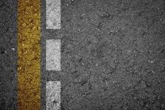 Οδική σύσταση ασφάλτου με την κίτρινη λουρίδα και την άσπρη λουρίδα Στοκ Εικόνα