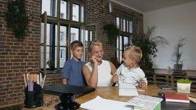 Ο ικανοποιημένος μέσης ηλικίας δάσκαλος, μαζί με την μικροί μαθητές, που χαίρονται για την ολοκλήρωση των μαθημάτων και της εργασ φιλμ μικρού μήκους