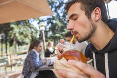 Ο ικανοποιημένος τύπος πίνει το χυμό φρούτων του, τα μάτια του είναι κλειστά Κρατά burger στο αριστερό χέρι του στοκ φωτογραφία