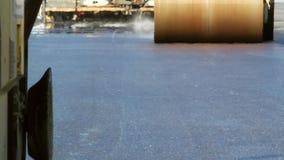 Οδικοί κύλινδροι που ισοπεδώνουν το φρέσκο πεζοδρόμιο ασφάλτου απόθεμα βίντεο