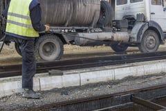 Οδικός εργαζόμενος που ψεκάζει με το χέρι το γαλάκτωμα πίσσας στοκ φωτογραφίες με δικαίωμα ελεύθερης χρήσης