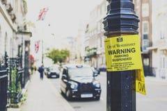 Οδικό σημάδι στο Λονδίνο με την αρχιτεκτονική ένα αμάξι ταξί bokeh σε Mayfair στοκ φωτογραφία