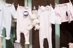 Ο ιματισμός μωρών και teddy αντέχει στο παράθυρο Στοκ εικόνα με δικαίωμα ελεύθερης χρήσης