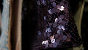 Ο ιματισμός που γίνεται από τα πορφυρά τσέκια κρεμά σε μια κρεμάστρα απόθεμα βίντεο