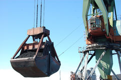 Ο λιμενικός γερανός φορτίου φορτώνει τον άνθρακα στο λιμένα ποταμών Kolyma στοκ φωτογραφία