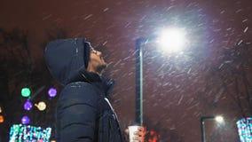 Ο ινδικός τύπος στα γυαλιά εξετάζει το πετώντας χιόνι το βράδυ στο πάρκο απόθεμα βίντεο