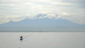 Ο ινδονησιακός ψαράς πιάνει ένα ψάρι κατά τη διάρκεια μιας τροπικής βροχής Στοκ Εικόνα