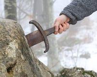 Ο ιππότης προσπαθεί να αφαιρέσει το ξίφος Excalibur στην πέτρα Στοκ Εικόνες