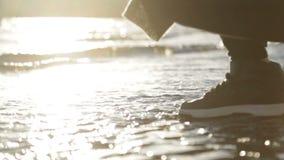 Ολισθήσεις χεριών πέρα από τα κύματα στο ηλιοβασίλεμα απόθεμα βίντεο