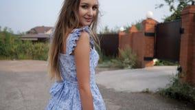 Ο ισχυρός άνεμος φυσά την όμορφη γυναικεία δίκαιη τρίχα που φορά το μπλε φόρεμα φιλμ μικρού μήκους