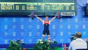 Ο ισχυρός αθλητής κοριτσιών ανυψώνει επάνω το βάρος στη σκηνή ενάντια στον πίνακα απόθεμα βίντεο