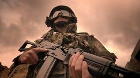 Ο ισχυρός ανώτερος υπάλληλος στην κάλυψη στέκεται στο νεφελώδες υπόβαθρο ουρανών, που κρατά το αυτόματο πυροβόλο όπλο, απεικόνιση απόθεμα βίντεο