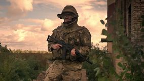 Ο ισχυρός αυθεντικός στρατιώτης στέκεται resistantly την κάλυψη και το κράνος με το αυτόματο πυροβόλο όπλο στα χέρια, απόθεμα βίντεο
