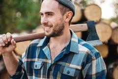 Ο ισχυρός γενειοφόρος υλοτόμος κρατά το τσεκούρι στον ώμο του στην αποθήκη εμπορευμάτων των κούτσουρων στοκ φωτογραφία με δικαίωμα ελεύθερης χρήσης