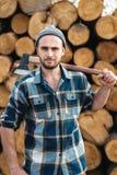 Ο ισχυρός γενειοφόρος υλοτόμος κρατά το τσεκούρι στον ώμο του στοκ εικόνα με δικαίωμα ελεύθερης χρήσης