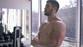 Ο ισχυρός μυϊκός αθλητής θερμαίνει μετά από τη δύναμη workout στην οικοδόμηση του μυός στην αθλητική λέσχη φιλμ μικρού μήκους