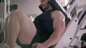Ο ισχυρός μυϊκός αθλητικός τύπος εκτελεί μια άσκηση στη μηχανή Τύπου ποδιών κατά τη διάρκεια της δύναμης εκπαιδευτικός να χτίσει  απόθεμα βίντεο
