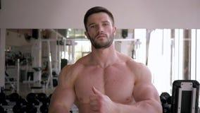 Ο ισχυρός μυϊκός αθλητικός τύπος θερμαίνει μετά από την κατάρτιση δύναμης στην οικοδόμηση του μυός στην αθλητική γυμναστική απόθεμα βίντεο