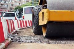 Ο ισχυρός συμπιεστής συμπιέζει και επίπεδα το χώμα μπροστά από την οδική ασφαλτόστρωση στοκ φωτογραφίες