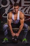 Ο ισχυρός τύπος, κάθεται οκλαδόν και προσπαθεί να ανυψώσει από το πάτωμα ένα μαύρο βάρος βαρύ μετάλλου Στο εσωτερικό στη γυμναστι στοκ εικόνες με δικαίωμα ελεύθερης χρήσης