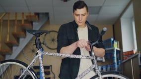 Ο ισχυρός όμορφος ειδικευμένος μηχανικός ατόμων συγκεντρώνεται στην επισκευή handlebar του σπασμένου ποδηλάτου στο μικρό εργαστήρ απόθεμα βίντεο