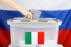 Ο ιταλικός πολίτης που κατοικεί στη Ρωσία πετά το ψηφοδέλτιο της σε ένα β στοκ φωτογραφίες