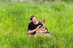 Ο ιδιοκτήτης εξετάζει το σκυλί του Γερμανική κατάρτιση ποιμένων Στοκ Φωτογραφία