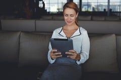 Ο ιδιοκτήτης επιχείρησης γυναικών ξαναδιαβάζει τις επιλογές στο μαξιλάρι αφής που έκανε το προσωπικό καθμένος στο νέο εστιατόριό  Στοκ εικόνα με δικαίωμα ελεύθερης χρήσης
