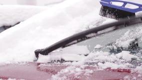 Ο ιδιοκτήτης καθαρίζει το αυτοκίνητό του από το χιόνι φιλμ μικρού μήκους