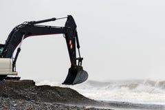 Ο κάδος εκσκαφέων εκσκάπτει τις πέτρες στην ακτή στο θυελλώδη καιρό Στοκ Εικόνες