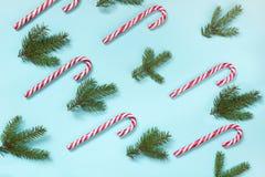Ο κάλαμος καραμελών Χριστουγέννων είπε ψέματα ομοιόμορφα στη σειρά στο μπλε υπόβαθρο Επίπεδος βάλτε και τοπ άποψη Στοκ εικόνα με δικαίωμα ελεύθερης χρήσης