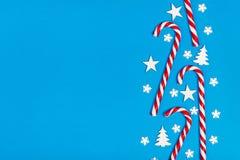 Ο κάλαμος καραμελών Χριστουγέννων είπε ψέματα ομοιόμορφα στη σειρά στο μπλε υπόβαθρο με διακοσμητικά snowflake και το αστέρι Επίπ Στοκ Εικόνα