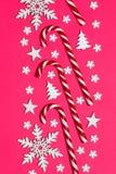 Ο κάλαμος καραμελών Χριστουγέννων είπε ψέματα ομοιόμορφα στη σειρά στο ρόδινο υπόβαθρο με διακοσμητικά snowflake και το αστέρι Επ Στοκ Φωτογραφία